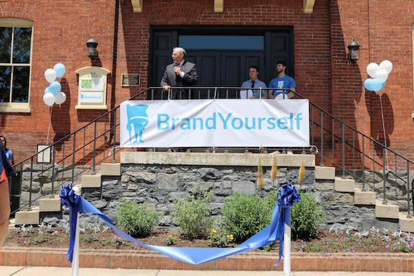 Mayor Rick Gray addresses the crowd while BrandYourself co-founders Patrick Ambron and Pete Kistler look on.